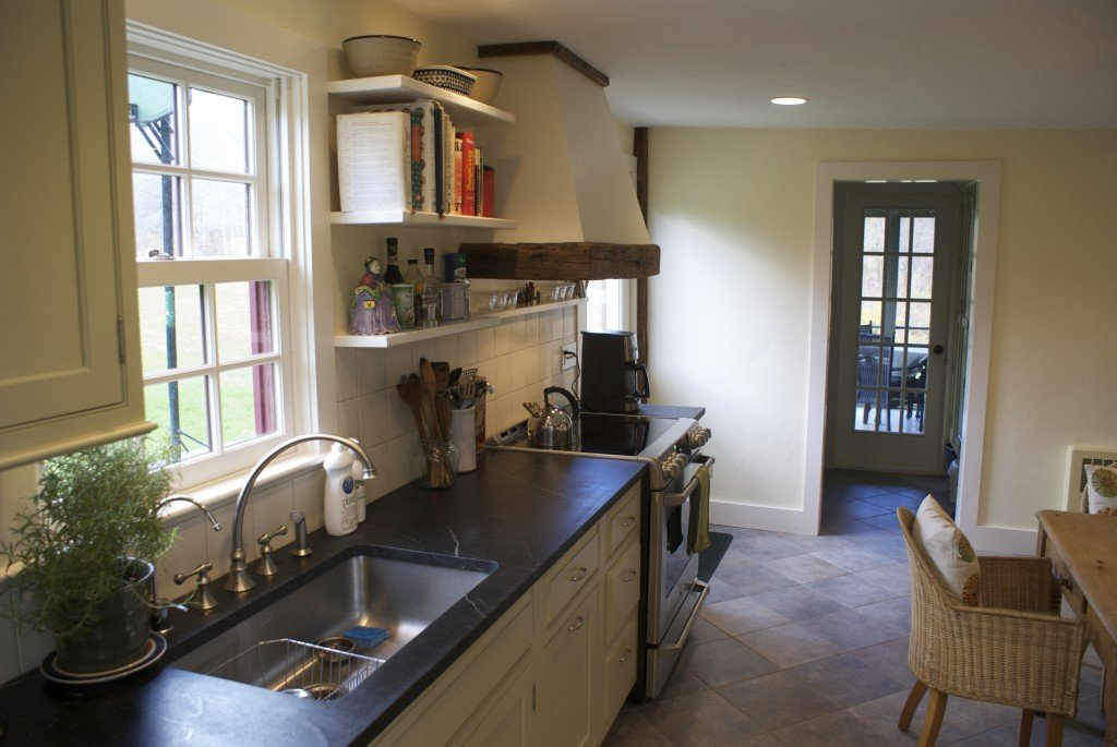 Open shelves, soapstone countertop, stainless single bowl undermount Elkay sink, custom hood of plaster and reclaimed beams in an old farmhouse kitchen, Dutchess county, NY