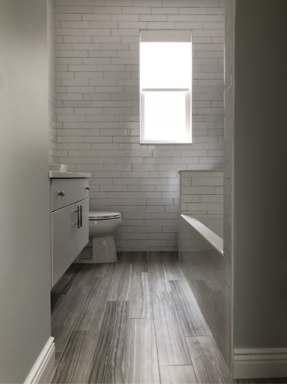 Light color tones with low contrast, combined with showing as much floor as possible creates a more spacious feeling in this small bath