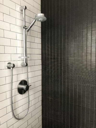 Restricting materials to slim black tile and white subway tiles. Keeping colors and materials to a minimum.
