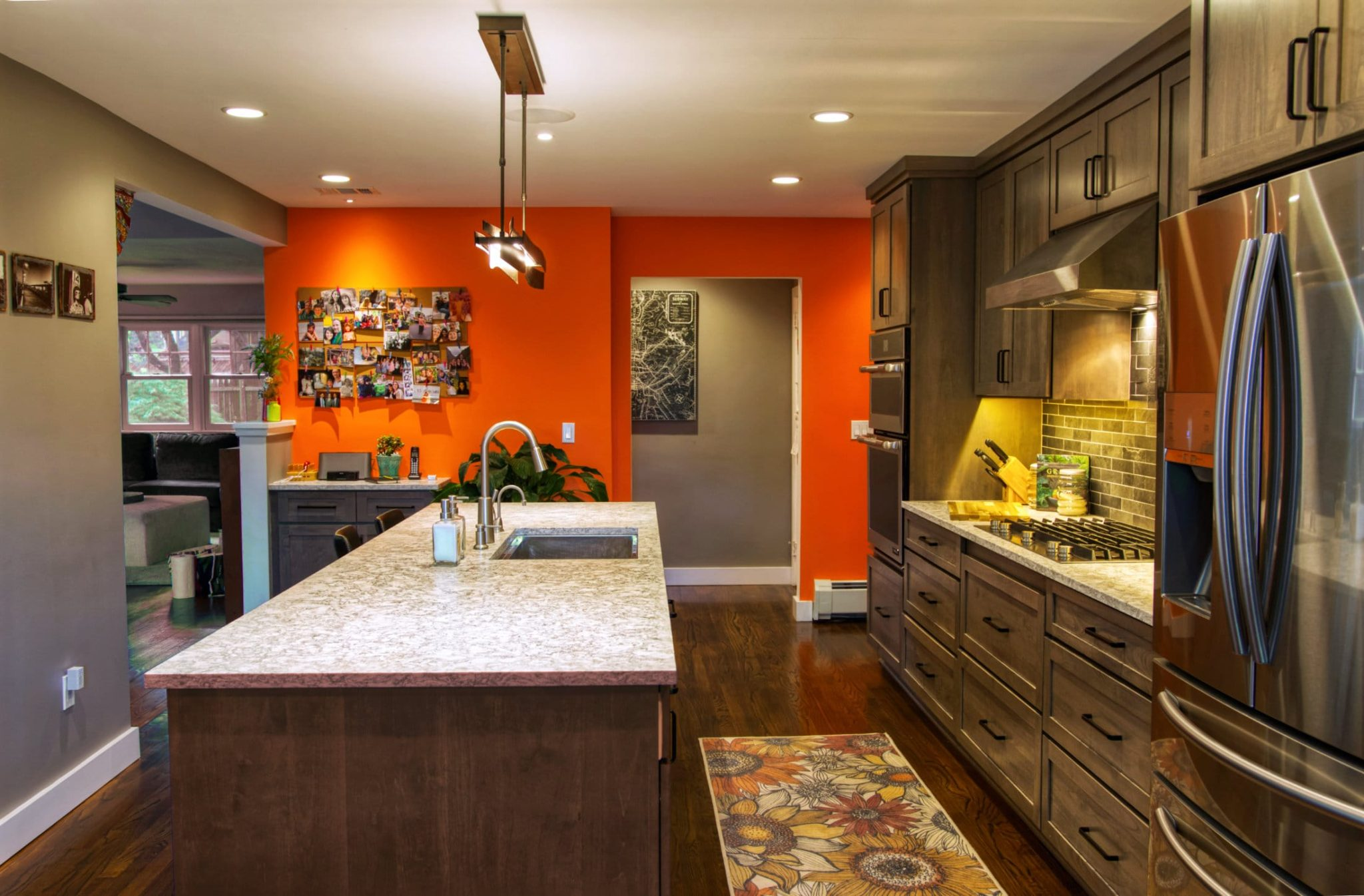 Kitchen Island with sink, and main run of cabinets, built in counter cooktop, refrigerator, exhaust hood