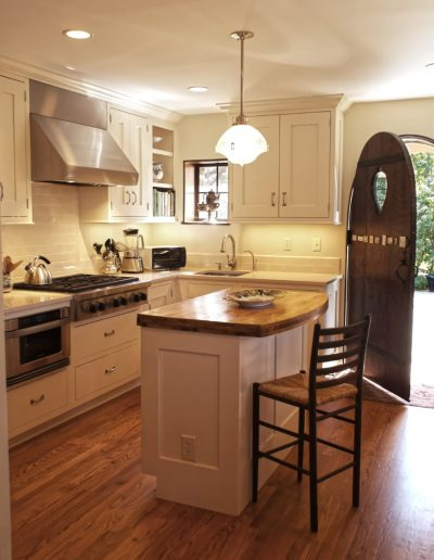 Creme Painted Cabinets in a Tudor Home's Kitchen with Traditional Pendant Light