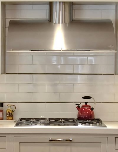 White Kitchen with Painted Cabinets, Cooktop with Stainless Hood and Elongated hand made tile backsplash with Bronze liner.