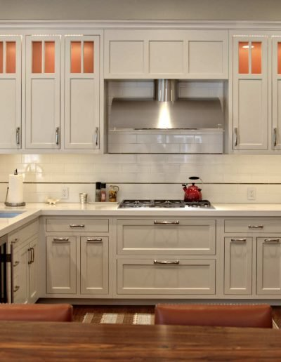 Inset flat panel cabinet doors in stone tone with terra cotta interiors for warm counterpoint in the kitchen
