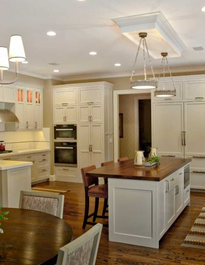 Metal finishes and style of lighting unify this White Kitchen along with Terra Cotta Colorations and Island with Mahogany Top