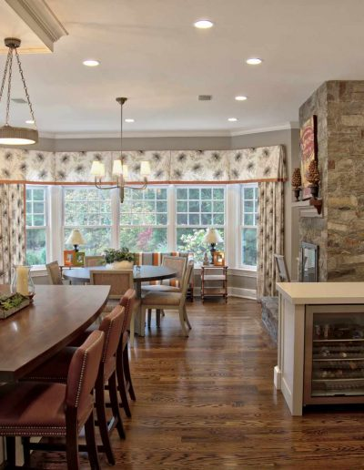 Open Plan Kitchen with Mahogany Island with Pendant lighting opens to a large Dining Room with eating area and fireplace.