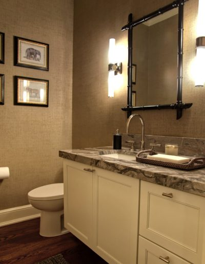 Powder room with grass cloth wallpaper and marbled countertops give this bathroom elegance