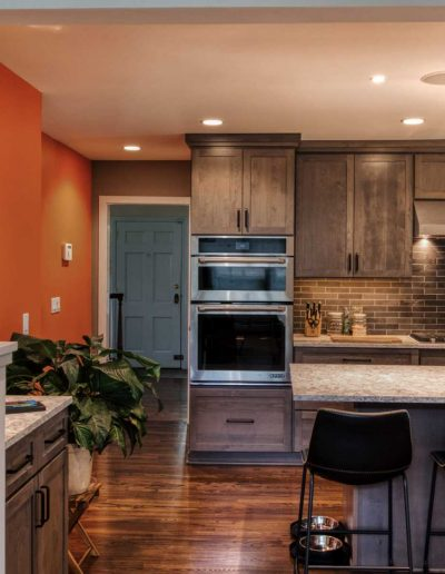 Strong orange wall and calm colors working together to lend extra personality to a home kitchen