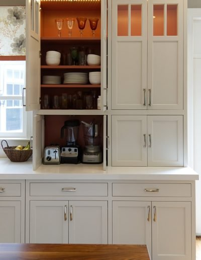 Floor to Ceiling White Cabinet with Open Door to show Dishes Inside